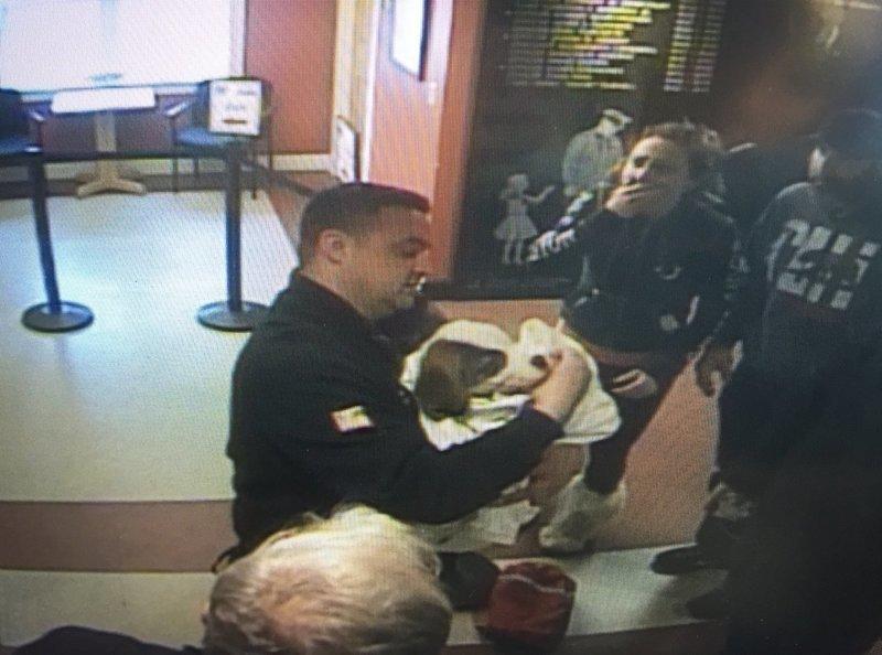 полицейский несет на руках собаку