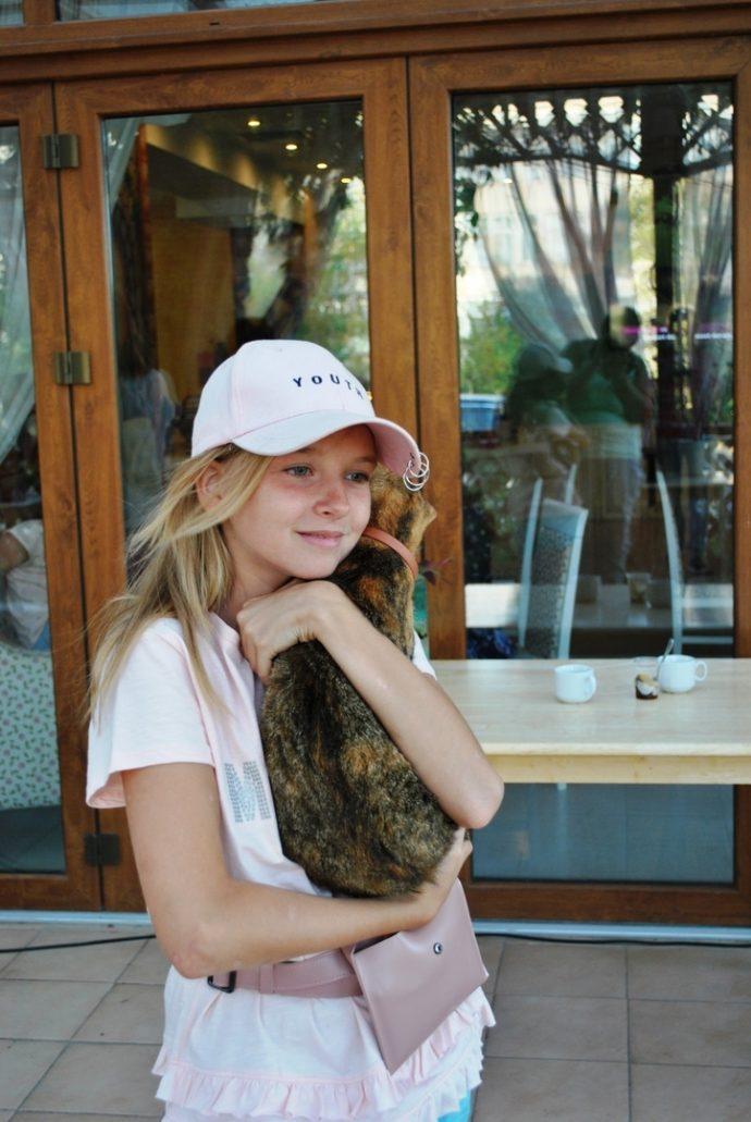 девочка в кепке с кошкой