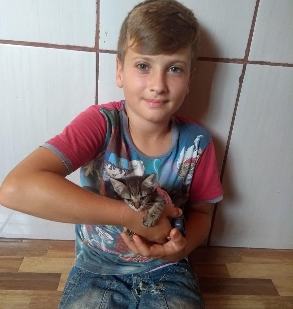 мальчик держит котенка