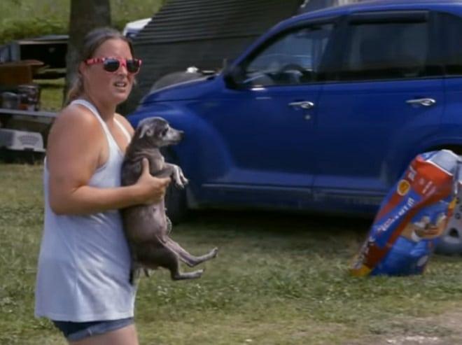 Девушка несет собаку